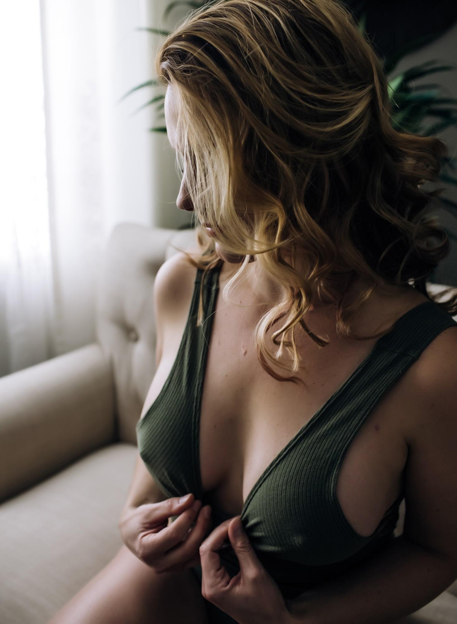 blonde-beauty-pulling-on-her-green-bodysuit