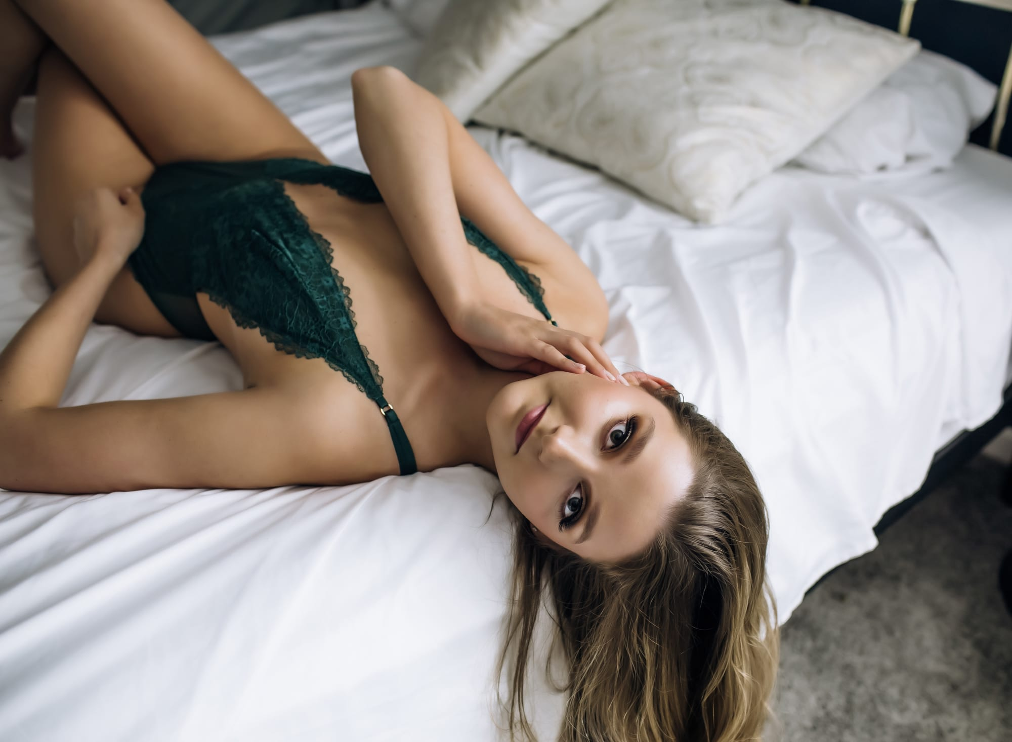 blonde-woman-in-green-bodysuit-laying-on-white-sheets