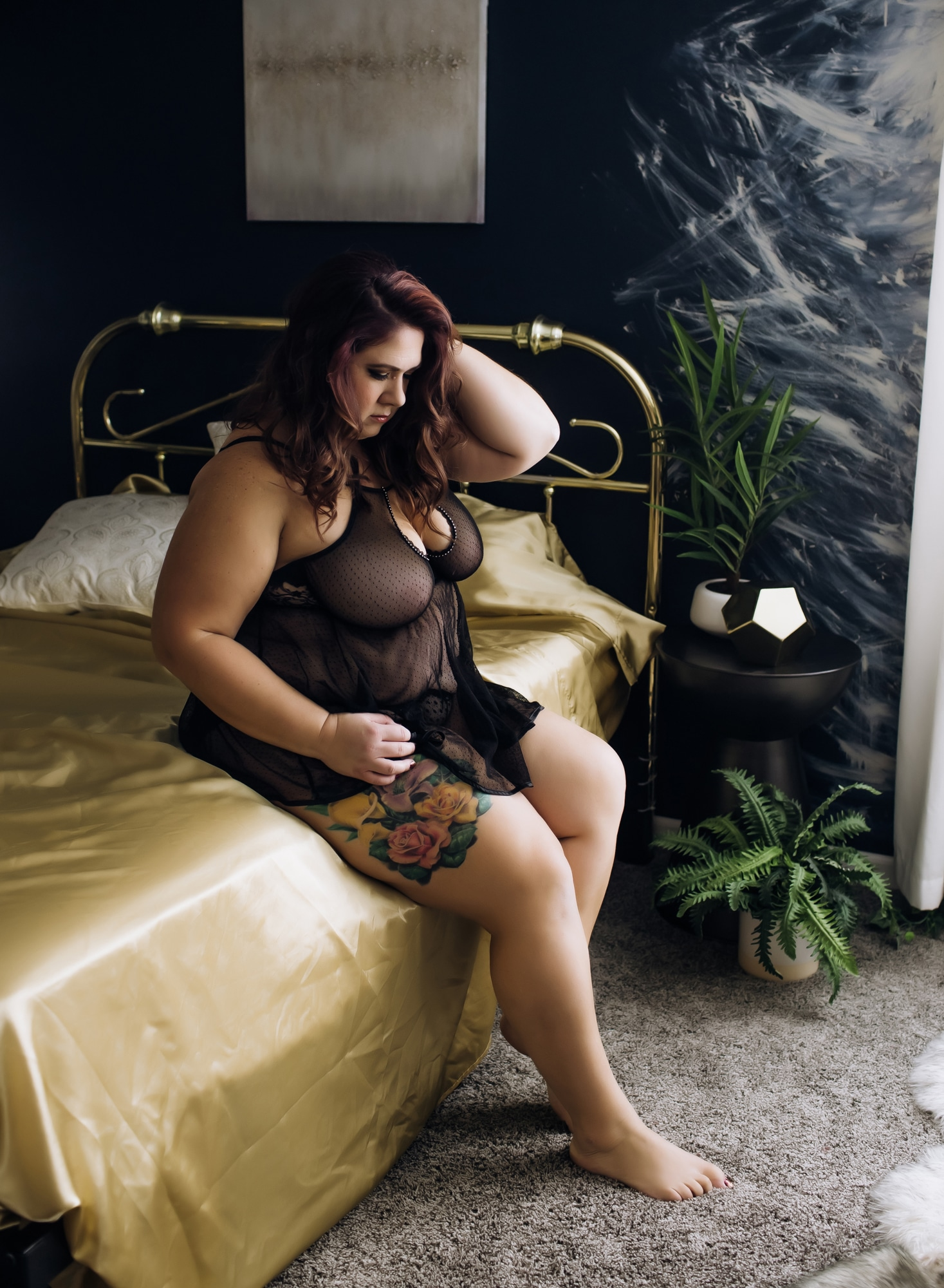 curvy-brunette-sitting-on-edge-of-bed-with-gold-sheets