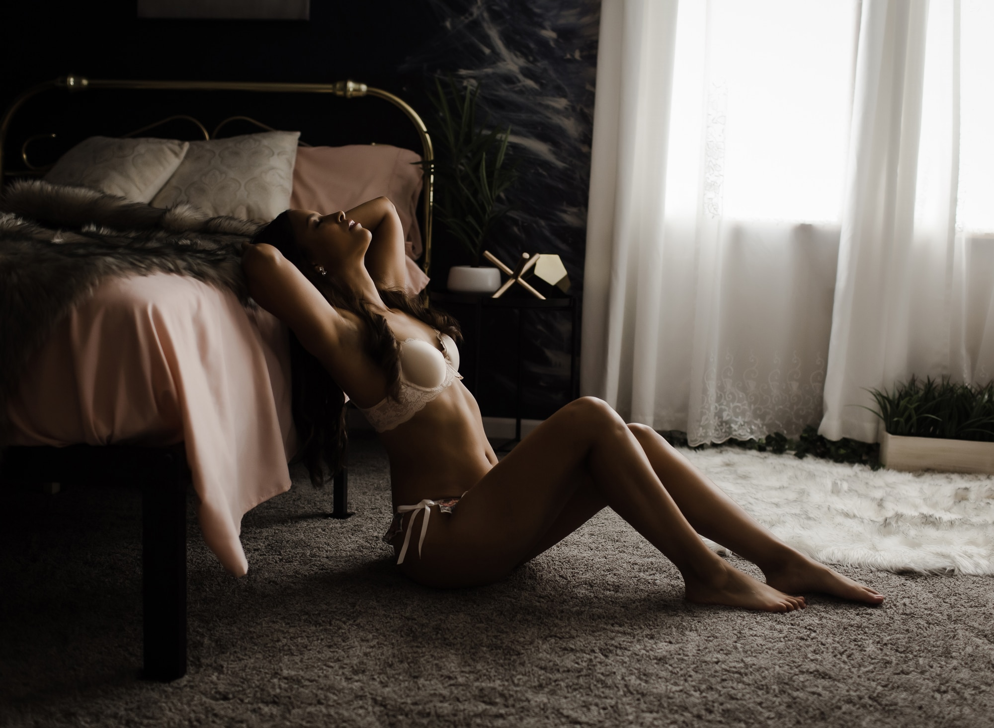 woman-sitting-on-floor-arching-back-over-bed-with-pink-sheets